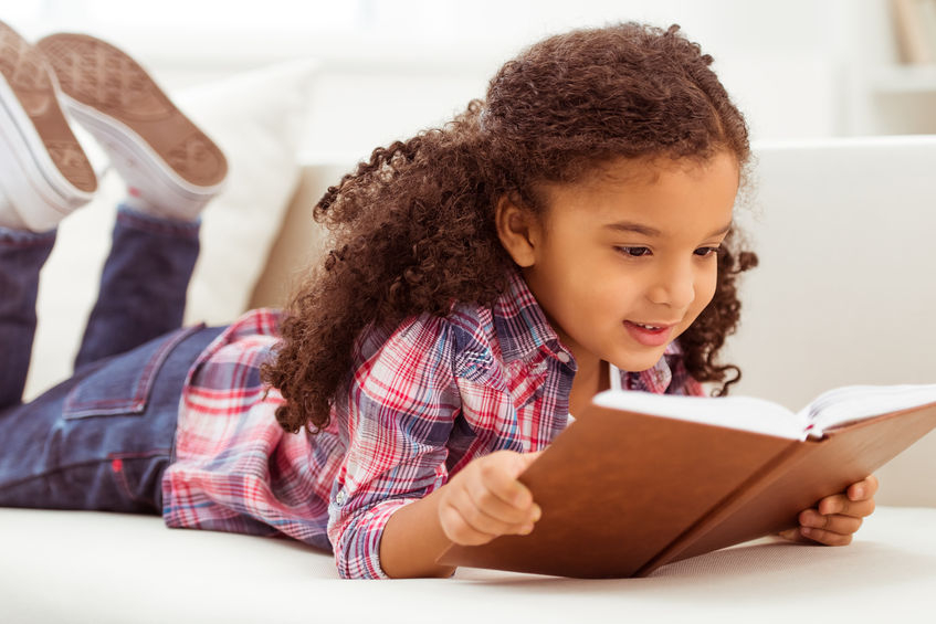 52354895 - cute little afro-american girl in casual clothes reading a book and smiling while lying on a sofa in the room.